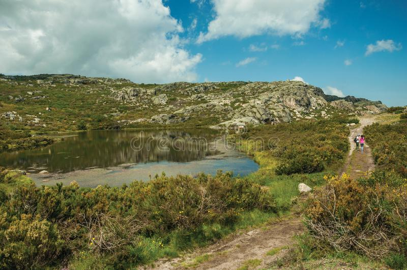 People on trail next to lake among rocky terrain royalty free stock image