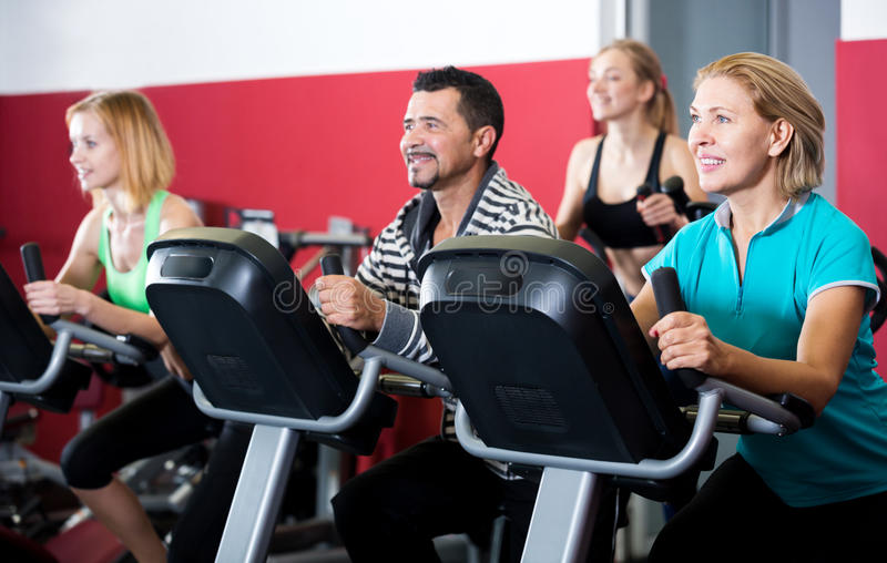 People training on exercise bikes together stock images