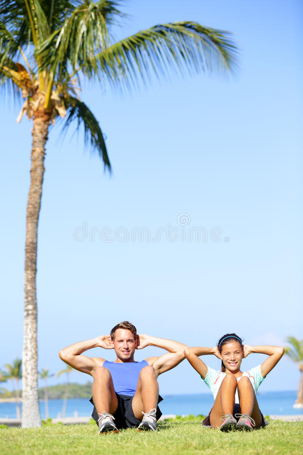 People training sit ups outside - fitness couple. People training sit ups outside. Fitness couple doing situps exercise during outdoor cross training workout royalty free stock photos
