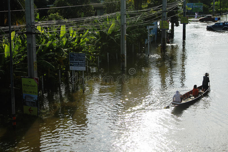 People travel by boat on the road during flood