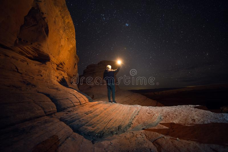 People Travel to scenic destination concept. Tourist man walking holding the light traveling in mountains and enjoy the night sky royalty free stock photos