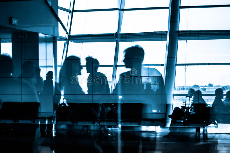 People traveling on airport silhouettes. Silhouettes of business people traveling on airport; waiting at the plane boarding gates stock photography