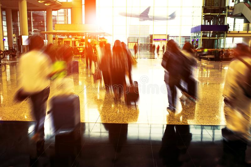 People with traveling luggage walking in airport terminal royalty free stock photo