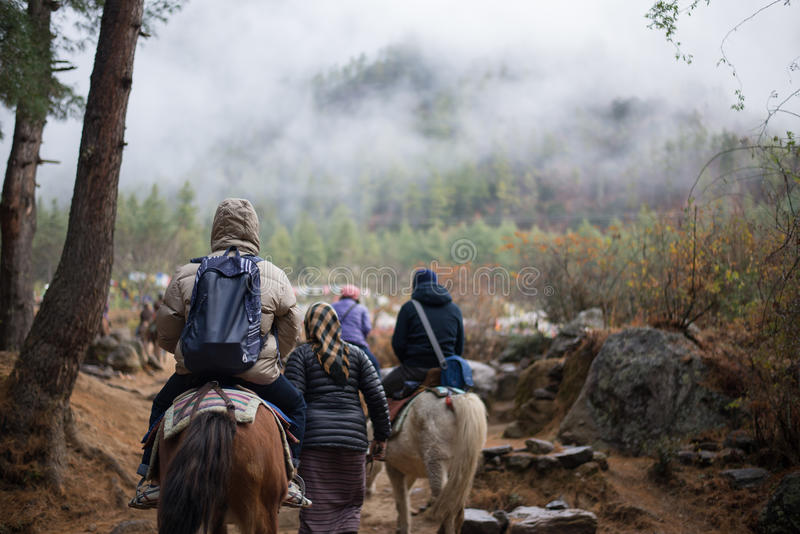 People traveling to Taktshang Goemba by horse. PARO - BHUTAN, DECEMBER 15 : People traveling to Taktshang Goemba by horse December 15, 2014 stock photo