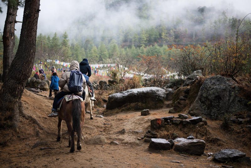 People traveling to Taktshang Goemba by horse. PARO - BHUTAN, DECEMBER 15 : People traveling to Taktshang Goemba by horse December 15, 2014 royalty free stock photo
