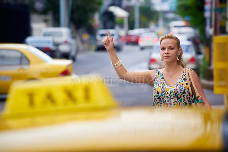 People travelling-business woman stopping yellow taxi stock photo