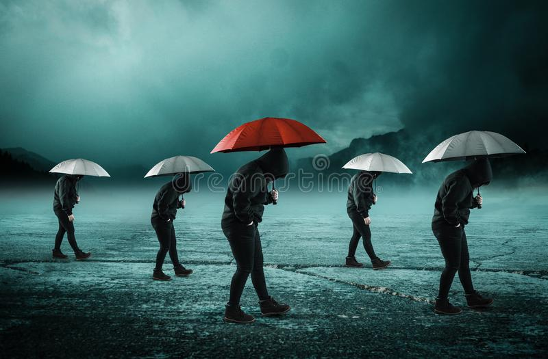 Out of the box concept. People with umbrella walking , the middle one has a red umbrella.Out of the box concept royalty free stock images