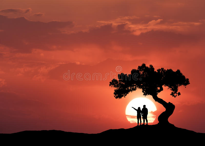People under the crooked tree on the background of sun stock images