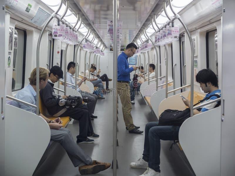 People using phones in the Metro stock image