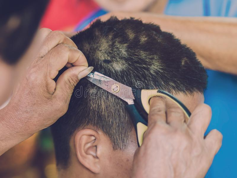 People using scissors to trim hair before ordination ceremony. Of Thai tradition royalty free stock photography