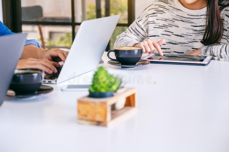 People using and working on laptop computer and tablet pc in office stock photography