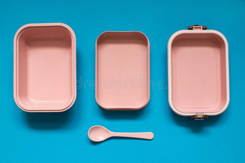 Empty pink bento lunch box with spoon on blue background stock photo