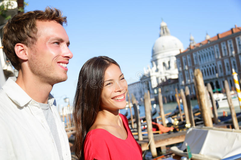 People in Venice. Couple in love traveling in Venice, Italy walking near a canal with boats. Happy young couple on travel vacation in Europe. Asian women and stock images