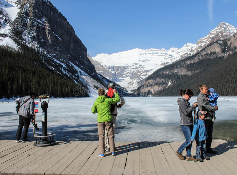 Tourists on banks of Lake Louise, Alberta, Canada. Tourists on wooden boardwalk along banks of Lake Louise, Alberta, Canada royalty free stock photos