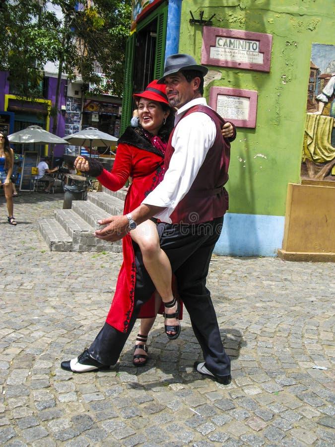 People visit Caminito Street in La Boca. BUENOS AIRES, ARGENTINA - JAN 26, 2015: tango dancer pose for tourists in Caminito Street, Buenos Aires, Argentina stock image