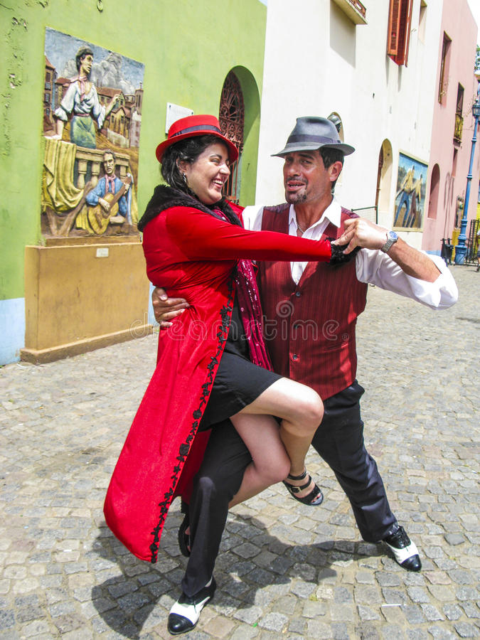 People visit Caminito Street in La Boca. BUENOS AIRES, ARGENTINA - JAN 26, 2015: tango dancer pose for tourists in Caminito Street, Buenos Aires, Argentina royalty free stock images