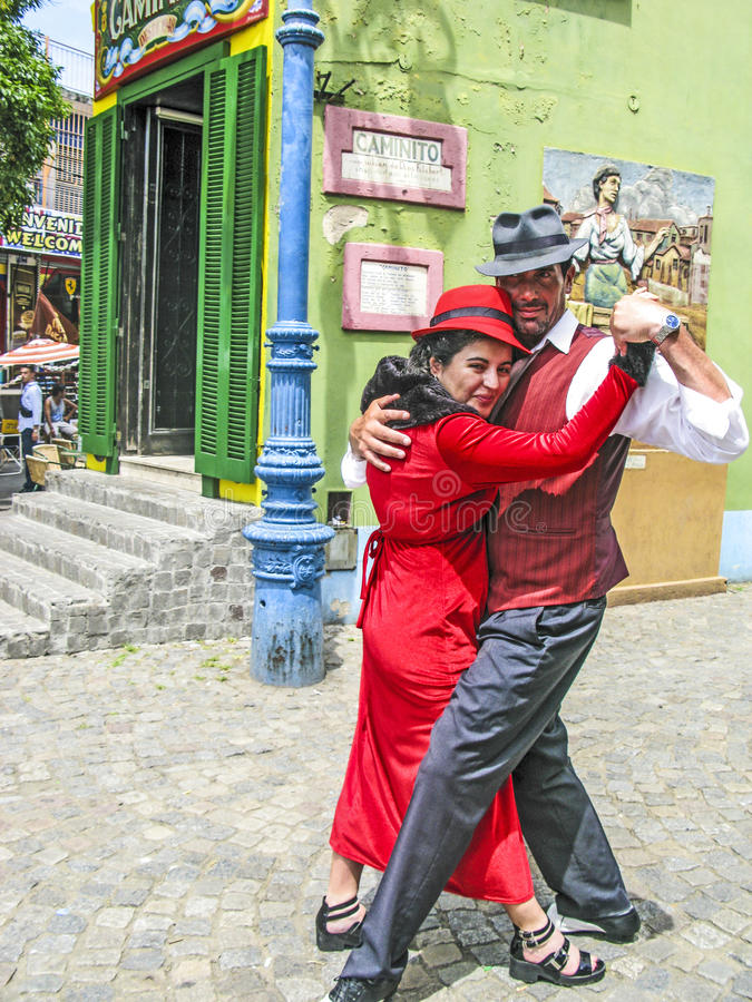 People visit Caminito Street in La Boca. BUENOS AIRES, ARGENTINA - JAN 26, 2015: tango dancer pose for tourists in Caminito Street, Buenos Aires, Argentina royalty free stock photos