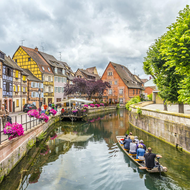 People visit little Venice in Colmar, France. COLMAR, FRANCE - JULY 3, 2013: people visit town of Colmar, France. Colmar has thousands of small canals and stock photography