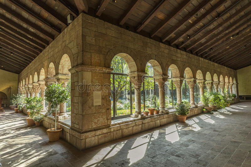 People visit the Sanctuary at the Cloisters museum in New York. NEW YORK, USA - OCT 22, 2015: Colonnade and garden at The Cloisters, the branch of The stock photo