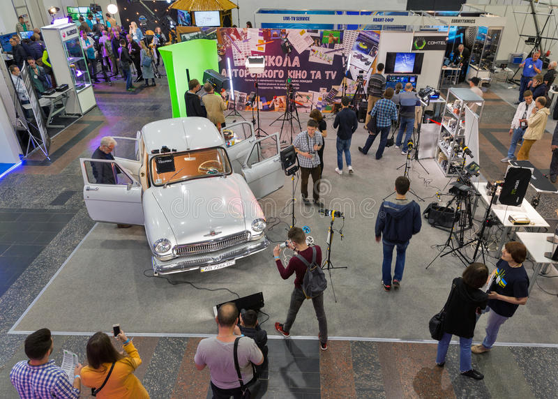 TV and Radio International Fair in Kiev, Ukraine. People visit School of Authors Cinema and TV booth with highlighted in multicolored lights GAZ-21 Volga royalty free stock photography