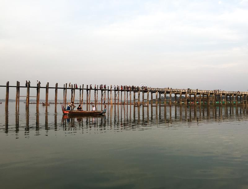 People visit U Bein Bridge by boat stock photography