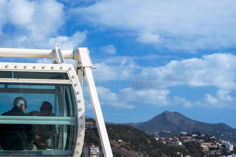 People visiting the Spanish city of Malaga from the cab of the Ferris wheel. Travel older couples. Beautiful landscape: city, mountains, houses against the royalty free stock photo