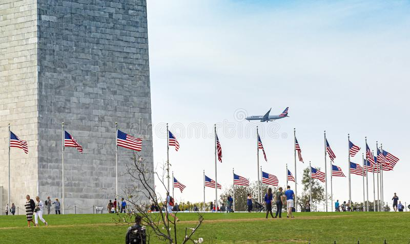 People visiting the Washington Monument with a commercial airplane landing in the background royalty free stock image