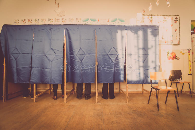 People vote in voting booth. People vote in a voting booth at a polling station royalty free stock images