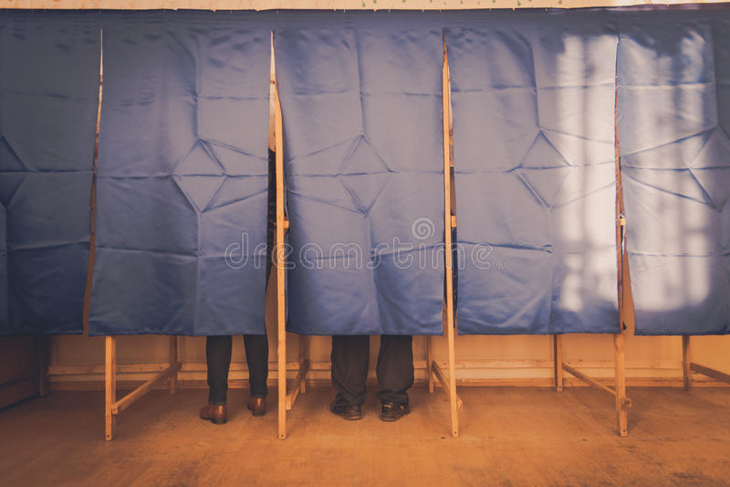 People vote in voting booth. People vote in a voting booth at a polling station royalty free stock photography