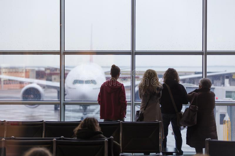 People waiting for airplane departure on a rainy day. People waiting for airplane departure at the airport gates on a rainy day. Bad rainy weather with storms royalty free stock photo