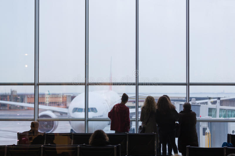 People waiting for airplane departure on a rainy day. People waiting for airplane departure at the airport gates on a rainy day. Bad rainy weather with storms royalty free stock photos