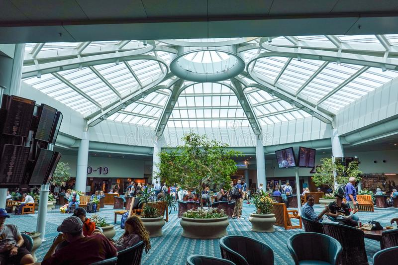 People waiting in an atrium area of the airport for their flights. Orlando, FL/USA-8/22/19: People waiting in an atrium area of the airport for their flights at royalty free stock photo