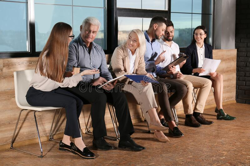People waiting for job interview in hall stock images