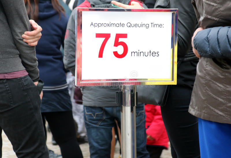 People waiting in a long queue. Focus on the information sign. Billboard with information about the time waiting beside line with many people waiting stock images