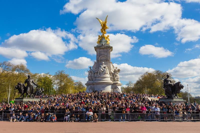 People waiting for palace guards at Victorial Memorial. London, England - 10 April 2017 - Tourists from all over the world wait arond the base of Victoria stock image