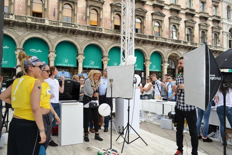 People waiting to be photographed for free at outdoors photo set `Brosway` in Milan Duomo square. Milan, Italy - June 9, 2016:  People on outdoors fun photo set stock images