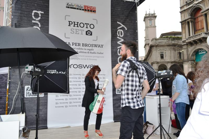 People waiting to be photographed for free on outdoors photo set `Brosway` in Milan Duomo square. Milan, Italy - June 9, 2016:  People on outdoors fun photo set stock photography