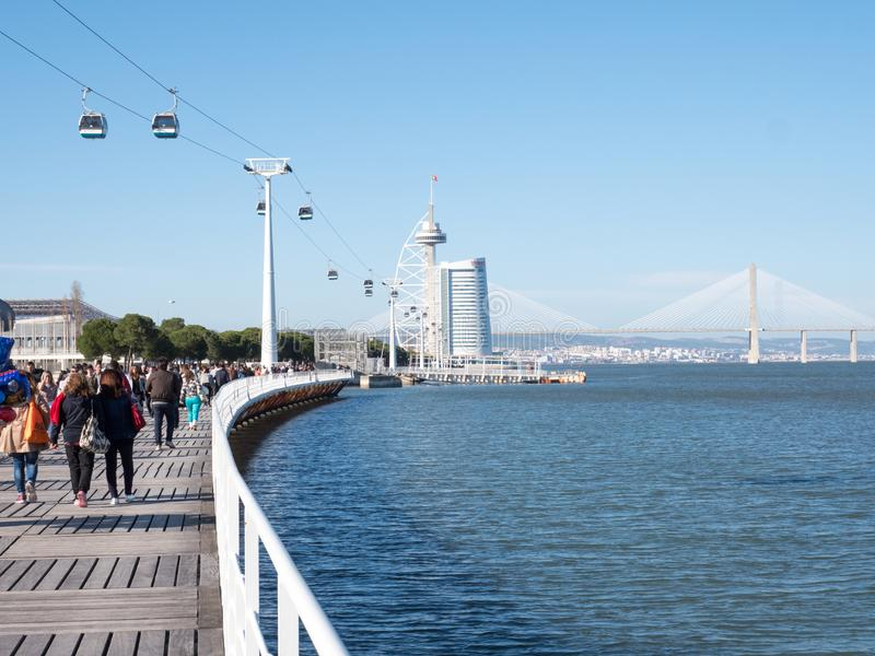 People wakling on a seafront parapet and looking to a sea and bridge in Lisbon stock photos
