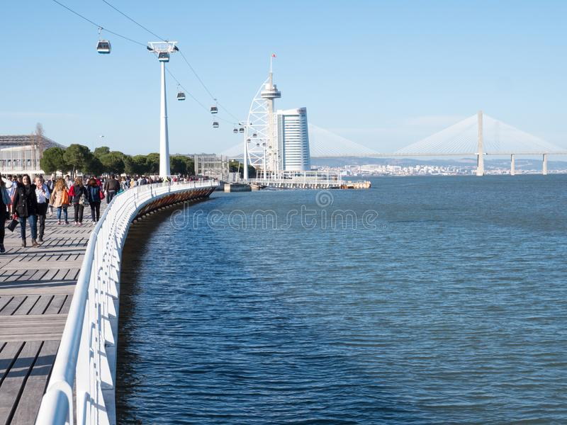 People wakling on a seafront parapet and looking to a sea and bridge in Lisbon royalty free stock images