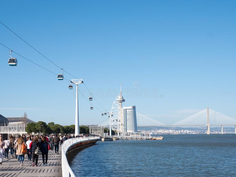 People wakling on a seafront parapet and looking to a sea and bridge in Lisbon stock image