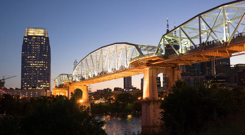People Walk Across Cumberland River Pedestrian Bridge Nashville. Night falls as pedestrians walk across a bridge for an event stock images