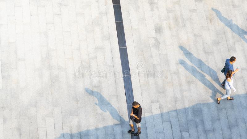 people walk on across the pedestrian concrete landscape with black silhouette shadow on ground (top aerial view) stock images