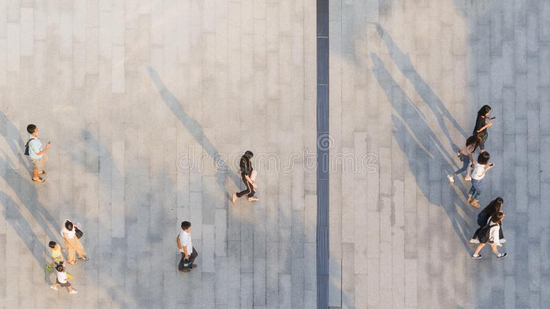 people walk on across the pedestrian concrete landscape with black silhouette shadow on ground (top aerial view) stock photo