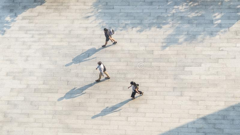 people walk on across the pedestrian concrete landscape with black silhouette shadow on ground (top aerial view) royalty free stock photos