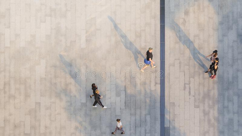 people walk on across the pedestrian concrete landscape with black silhouette shadow on ground (top aerial view) stock photography