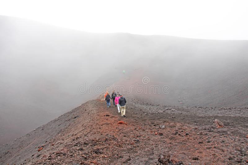 People Walk along the crater of Mount Etna. Black Volcanic Earth and Thick Fog on Mount Etna. Place for Text. The island of Sicily royalty free stock images