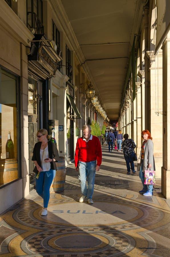 People walk along famous arcade on Rivoli Street, Paris, France. PARIS, FRANCE - SEPTEMBER 7, 2018: Unidentified people walk along famous arcade on Rivoli Street royalty free stock photo