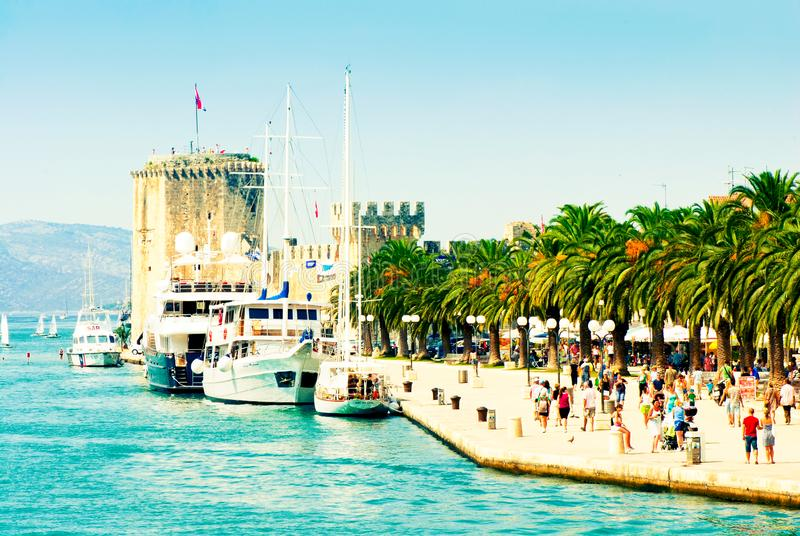 People walk along the picturesque pier of Trogir stock images