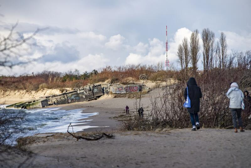 People walk along the sea, Melanarage beach, Klaipeda, Lithuania. People walk along the sea, MelanaragÄ— beach, Klaipeda, Lithuania. Dramatic clouds royalty free stock images