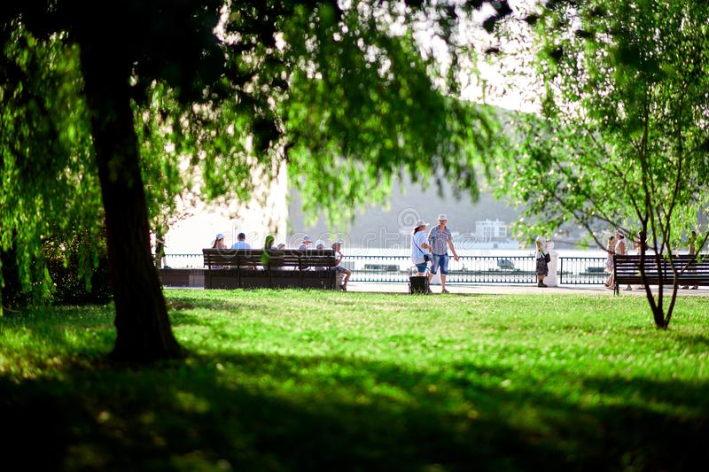 People walk along the waterfront beautiful green lawn royalty free stock photo